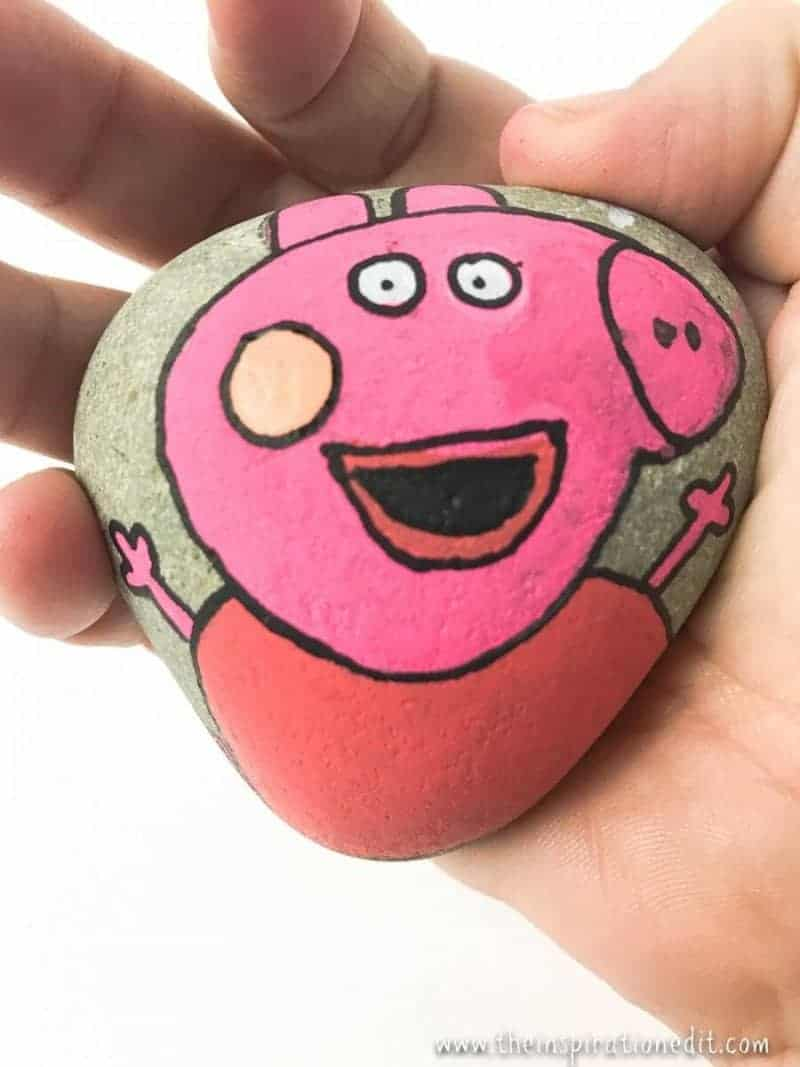 hand holding a Peppa Pig Rock painting