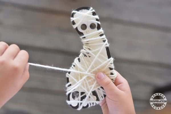 Halloween Art Projects the completed yarn mummy. A foot wrapped in white yarn with googly eyes.