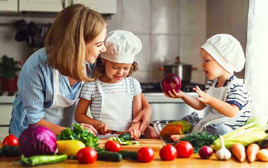 Healthy eating. Happy family mother and children prepares vegetable salad in kitchen. Learning While You Cook