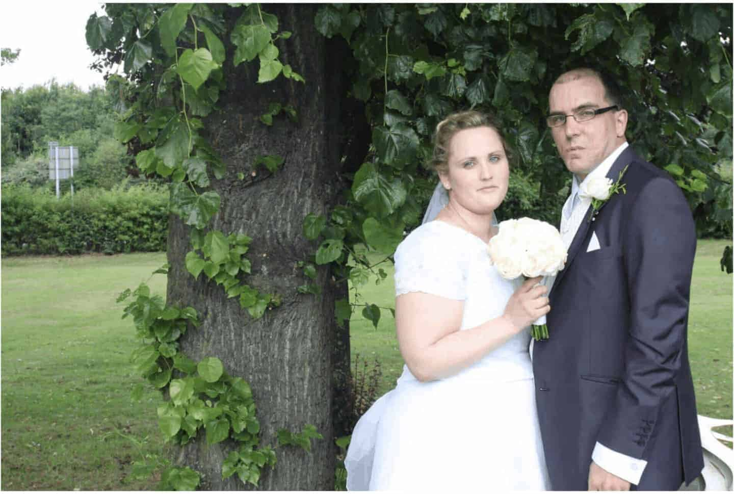 angela and john milnes wedding photo. a bride and groom standing bu a tree and holding flowers.