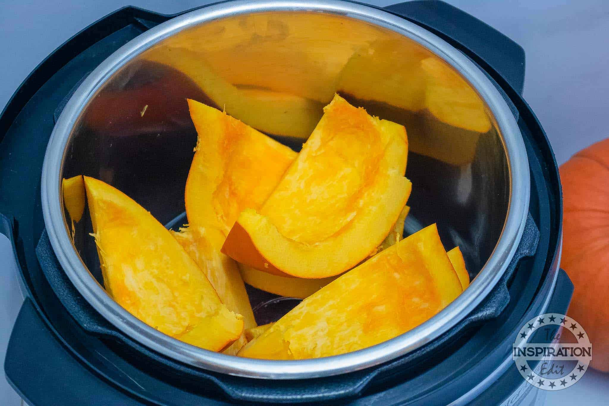 placing pumpkin into instant pot for pumpkin puree