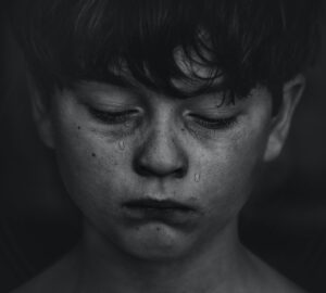 a child crying and looking sad due to a bully